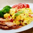 Scrambled eggs with bacon - Stock Photo