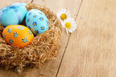 Nest with Easter eggs on the wooden table — Stock Photo