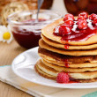 Delicious pancakes with raspberries on the wooden kitchen table — Stock Photo #18940061