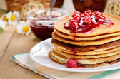 Delicious pancakes with raspberries on the wooden kitchen table — Stock Photo