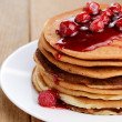 Delicious pancakes with raspberries on the wooden kitchen table — Stock Photo #20995225