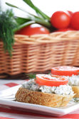 Cottage cheese bruschettas and vegetable basket — Stock Photo