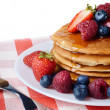Pancakes with berries and honey over white — Stock Photo