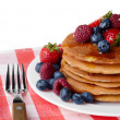 Pancakes with berries and honey over white — Stock Photo #34590371