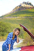 Young woman near broken car speaking by phone — Photo