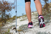 Female feet and trekking stick — Stockfoto