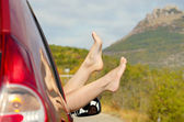 Female feet stick out of car window — Stock Photo