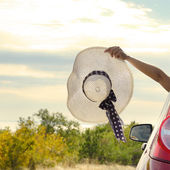 Woman shows sun hat from car — Stock Photo
