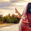 Female feet stick out of car window — Stock Photo #43750657