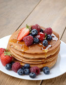 Pancakes with berries and honey closeup — Stock Photo
