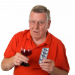 Old man with red wine and pills — Stock Photo
