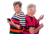 Two senior women communicating with cellphones — Stock Photo