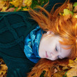 Beautiful woman lying on fall leaves — Stock Photo