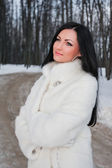 Young brunette woman in white fur coat — Stock Photo