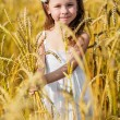 Little girl among wheat ears — Stock Photo