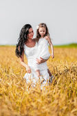 Mother and daughter among wheat ears — Stock Photo