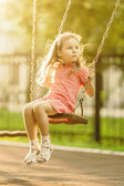 Pretty little girl swinging on seesaw beneath bright shining — Stock Photo