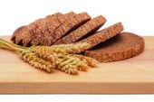 Rye malt bread and wheat ears — Stock Photo