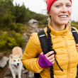 Woman hiking in mountains with akita dog — Stock Photo