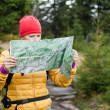 Woman hiking and reading map in forest — Stock Photo #13679788
