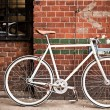 City bicycle on red wall, vintage style — Stock Photo #13679790