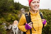 Mujer senderismo en las montañas con perro akita — Foto de Stock