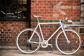 City bicycle on red wall, vintage style — Stok fotoğraf