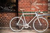Kırmızı duvar, vintage tarzı şehir bisiklet — Stok fotoğraf