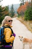 Woman hiking in mountains with akita dog — Stock Photo