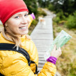 Woman hiking and reading map in forest — Stock Photo