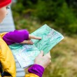 Woman hiking and reading map in forest — Stock Photo #14068263