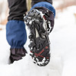 Walking legs and shoes on snow trail in winter — Stock Photo