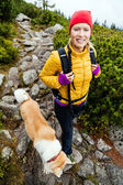 Woman hiking in mountains and walking akita dog — Stock Photo