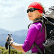 Foto Stock: Woman hiking with backpack in mountains