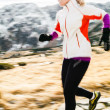 Young woman running in mountains on winter fall sunny day — Stock Photo