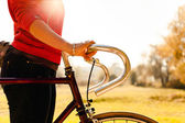 Woman cycling on bicycle in autumn park — Stockfoto