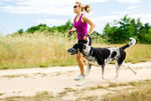 Woman runner running, walking dog in summer nature — Stock Photo
