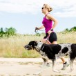 Woman runner running, walking dog in summer nature - Stock Photo