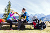 Couple hikers camping and drinking in mountains — Stock Photo