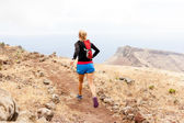 Young woman trail running in mountains — Stock Photo