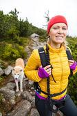 Vrouw wandelen in de bergen met akita hond — Stockfoto