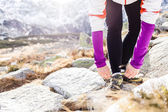 Runner tying sport shoe in mountains on trail — Stock Photo
