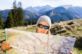 Woman hiker reading map in mountains — Stock Photo