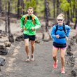 Couple trail running in forest — Stock Photo