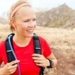 Young woman running in mountains on sunny day — Stock Photo