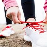 Постер, плакат: Woman runner tying sport shoes