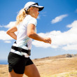 Young woman running in mountains on sunny summer day — Stock Photo