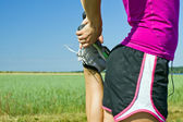 Woman runner stretching outdoors — Stock Photo
