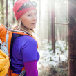 Stock Photo: Womhiking in winter forest sunlight