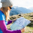 Woman reading map in mountains — Stock Photo